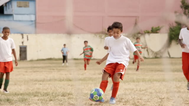 Brazilian boy shoots penalty kick and scores goal at youth soccer practice
