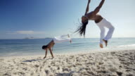 Brazilian capoeira masters flip across beach and roar at camera in slow motion
