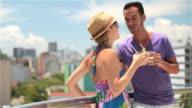 Brazilian couple chat intimately on hotel rooftop overlooking Rio skyline