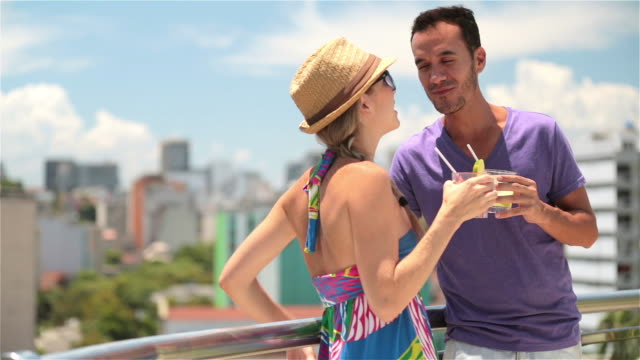 Brazilian couple chat intimately on hotel rooftop overlooking Rio skyline