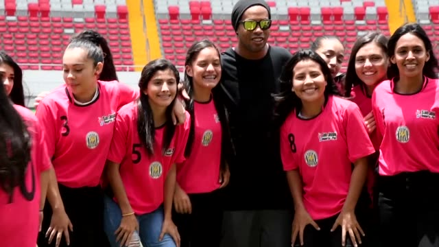 Brazilian football hero Ronaldinho poses for photos with young soccer players Friday on the field at the National Stadium in San Jose on the eve of a...