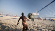 Brazilian footvolley player runs to kick soccer ball to his partner who sends it over the net in slow motion