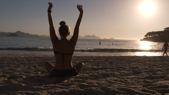 Brazilian girl stretches with arms overhead, lowers and twists on Copacabana Beach