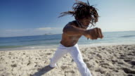Brazilian martial artist with dreadlocks throws punch at camera