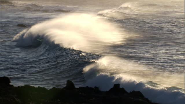 Breakers roll onto rocky coast at sunrise, Easter Island