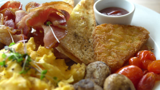 Breakfast dish with egg , bacon , sausage , bread and other
