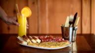 Breakfast dish with eggs, tomato, bread and fresh orange juice
