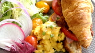 Breakfast dish with scrambled eggs and vegetable and Croissant sandwich with crispy bacon ham cheese inside