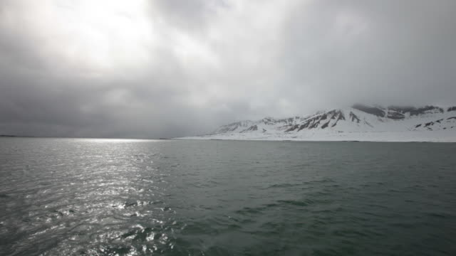 Breathtaking arctic landscape seen from a sailing boat on Isfjorden on the Spitsbergen island, Svalbard Archipelago, Norway; cloudy stormy weather