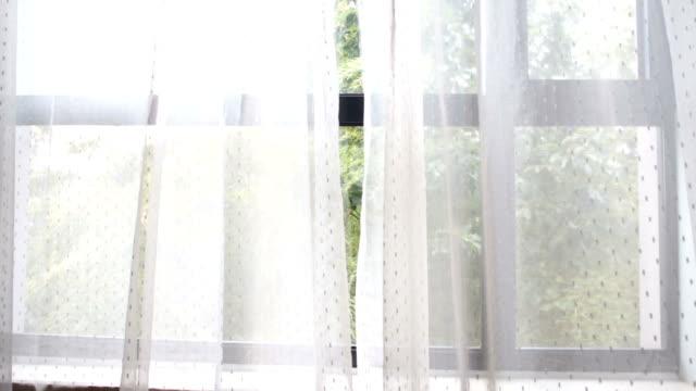 breeze einen Vorhang durch ein offenes Fenster
