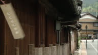 A breeze rustles wind-bells hanging from eaves as traffic travels past a row of old houses in Mino, Japan.