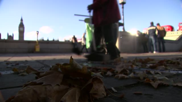 Theresa May makes statement to Commons on Brexit talks Westminster EXT Street sweeper sweeping Autumn leaves from footpath with Houses of Parliament...