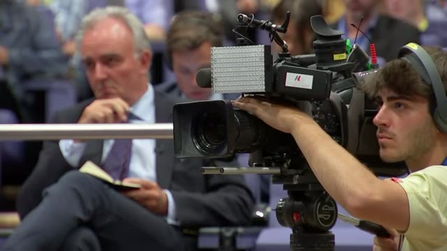 Third round of negotiations come to an end TV camera at press conference with reporter seen sat behind