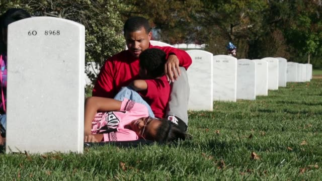 Brianna Bryson 12 Jaylen Bryson 5 and their father Steve Bryson spend time visiting the grave of Steve's father US Army Col Gene Bryson on Veterans...