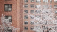 brick apartment building in snow - day