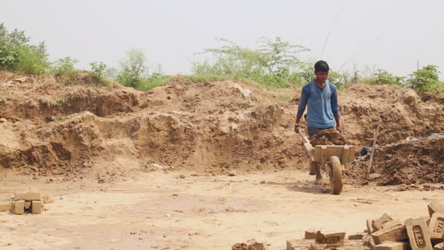 Brick factory worker filling cart with clay, Haryana, India
