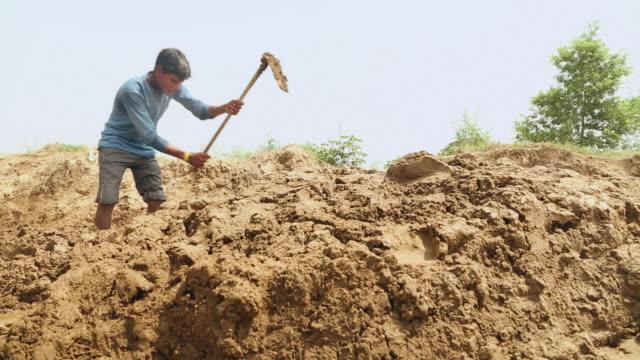 Brick factory worker mixing clay, Haryana, India