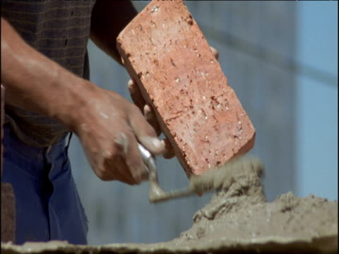 Brick layer places bricks and mortar into wall, South Africa