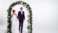 Bridal couple walking through archway