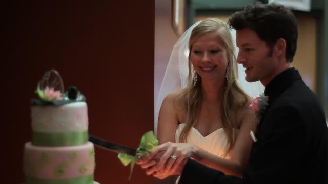 HANDHELD MEDIUM SHOT bride and groom cut wedding cake at reception