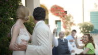 Bride and groom dancing and kissing, wedding guests toast them
