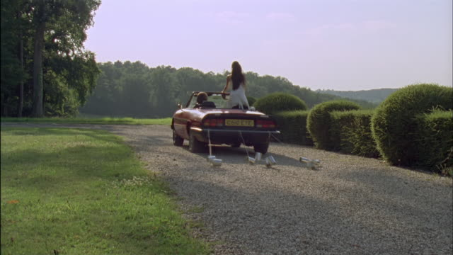 WS, Bride and groom driving red convertible car on gravel road, rear view, Chateau du Parc, Saint Ferme, France