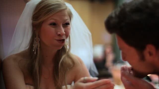 HANDHELD CLOSE UP bride and groom feed each other wedding cake