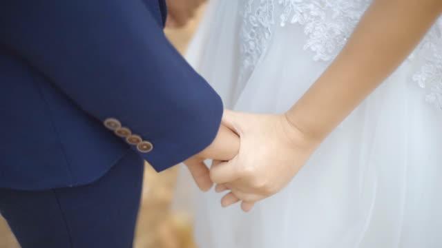 Bruid en bruidegom holding geruststellend hand samen in het park.