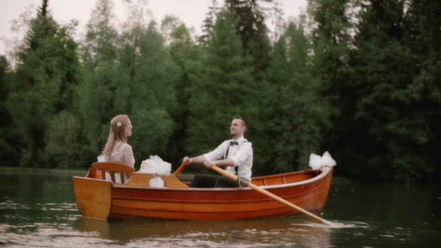 SLO MO Bride and groom in a rowing boat on a lake