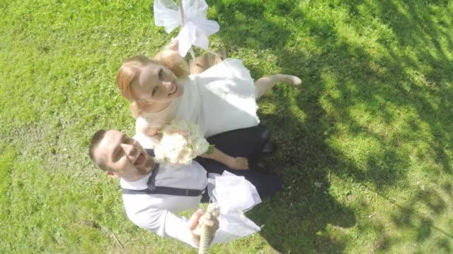 POV bruid en bruidegom zittend op een schommel in de zon