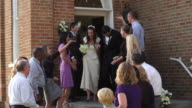 Bride and groom walking out of a church to rice-throwing guests.