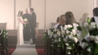 Bride and groom walking up the aisle to a preacher.