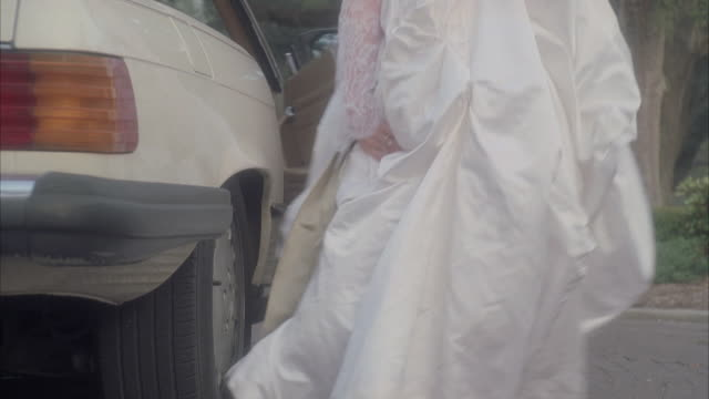 TD Bride entering white convertible and tossing out her garter before driving away / Tybee Island, Georgia, United States