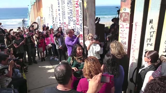 Bride Evelia Reyes and groom Brian Houston living on two sides of the US Mexico border get married at the border's fence as pro migrants NGO and...