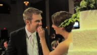 Bride laughs as she shoves wedding cake in groom's mouth