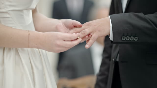 SLO MO Bride placing ring on groom's finger