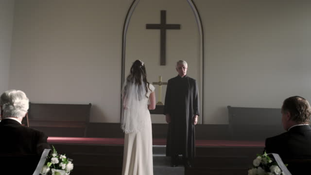 Bride standing without a groom in front of a preacher in a chapel.