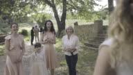Bride throwing bouquet to bridesmaids