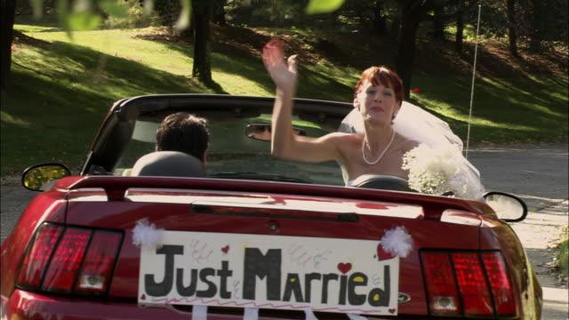WS PAN Bride waves from passenger seat as groom drives car away / Long Island, New York, USA