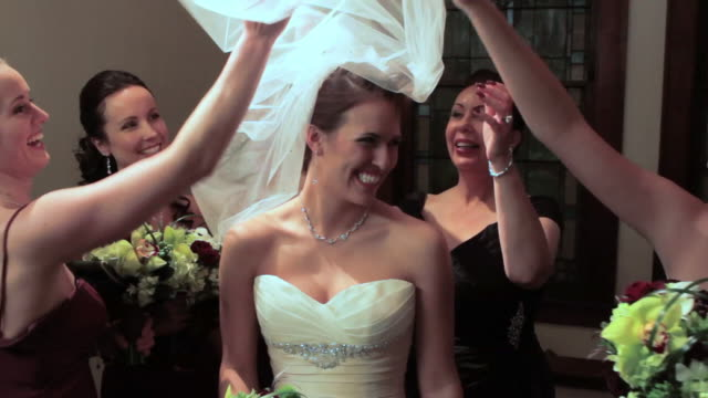 Bridesmaids playfully lift veil off bride's face