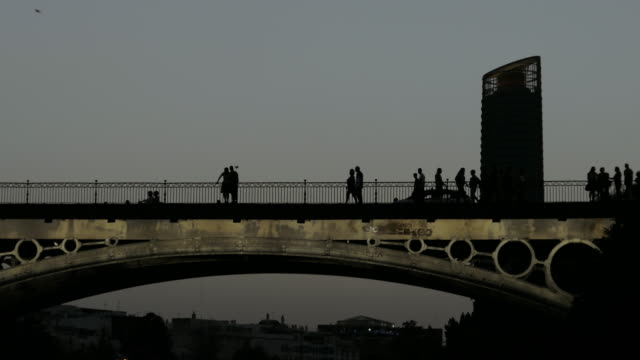 Bridge triana isabel II sevilla with people solhouette walking and Pelli tower in the background