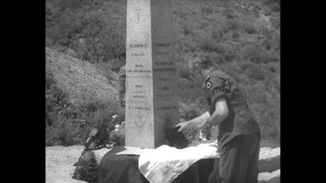 Brigadier General Tom Brodie with priest looking on unveils stone obelisk / flag arranged as makeshift altar covering priest and another bow and...