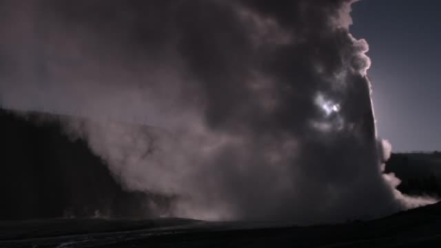 Bright moon shining behind eruption plume of geyser.