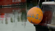 Bright orange buoy hanging on stern of fishing boat in harbor