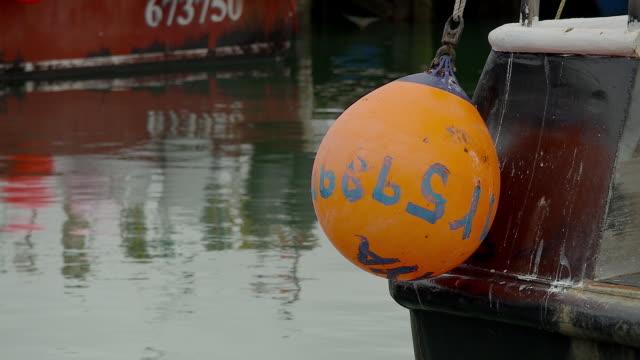 Bright orange buoy hanging on stern of fishing boat in harbor