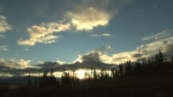 A brilliant sun sets behind passing clouds and evergreens.