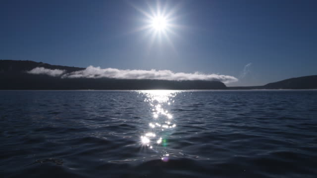 A brilliant white sun twinkles on the calm waters of Lake Tarawera in New Zealand.