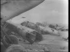 British 2nd South African Division Army trucks along desert / trucks past German cemetary / British tanks advance across desert toward smoke screen...
