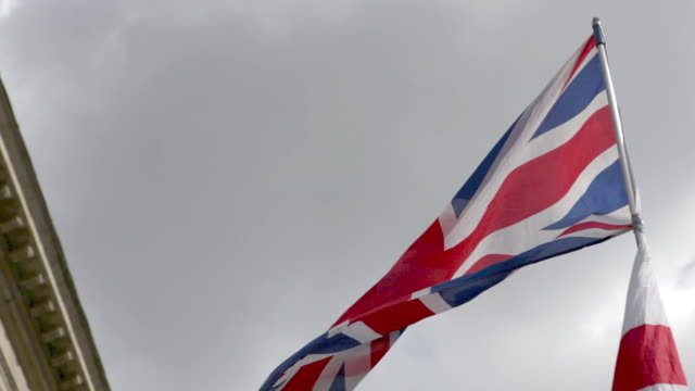 British and English flags blowing in breeze on overcast day