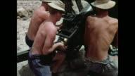 MONTAGE British artillery crew shells a hilltop / Aden, Yemen